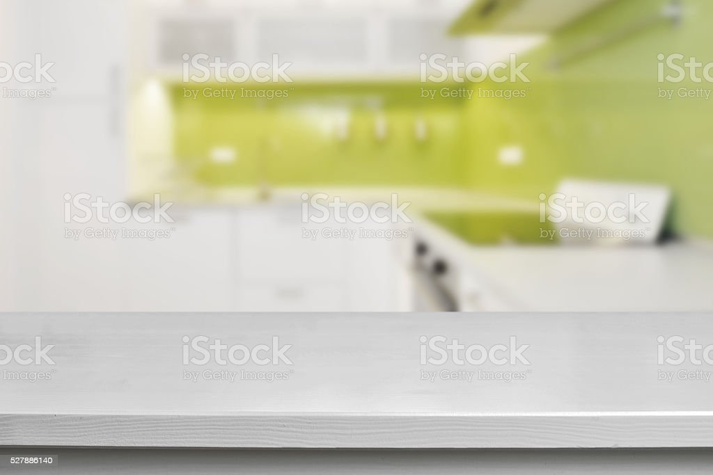 Empty white wooden table at the front and blurred kitchen at the...