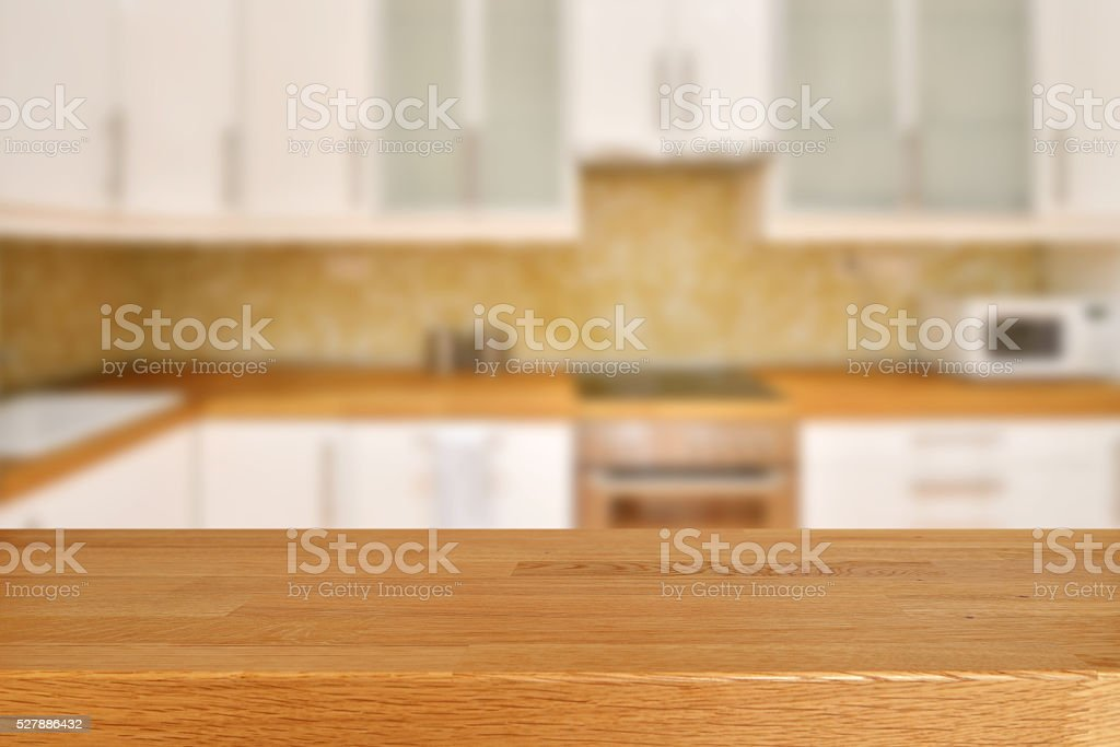 Empty wooden table at the front and blurred kitchen at the...