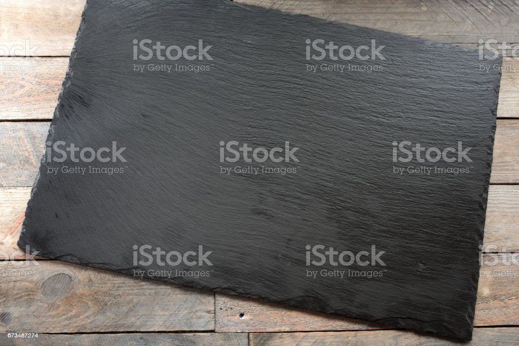 Wooden table with empty slate plate stock photo