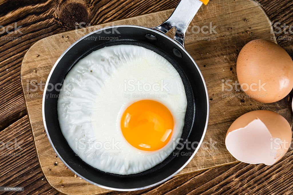 Wooden table with Fried Eggs (selective focus) stock photo