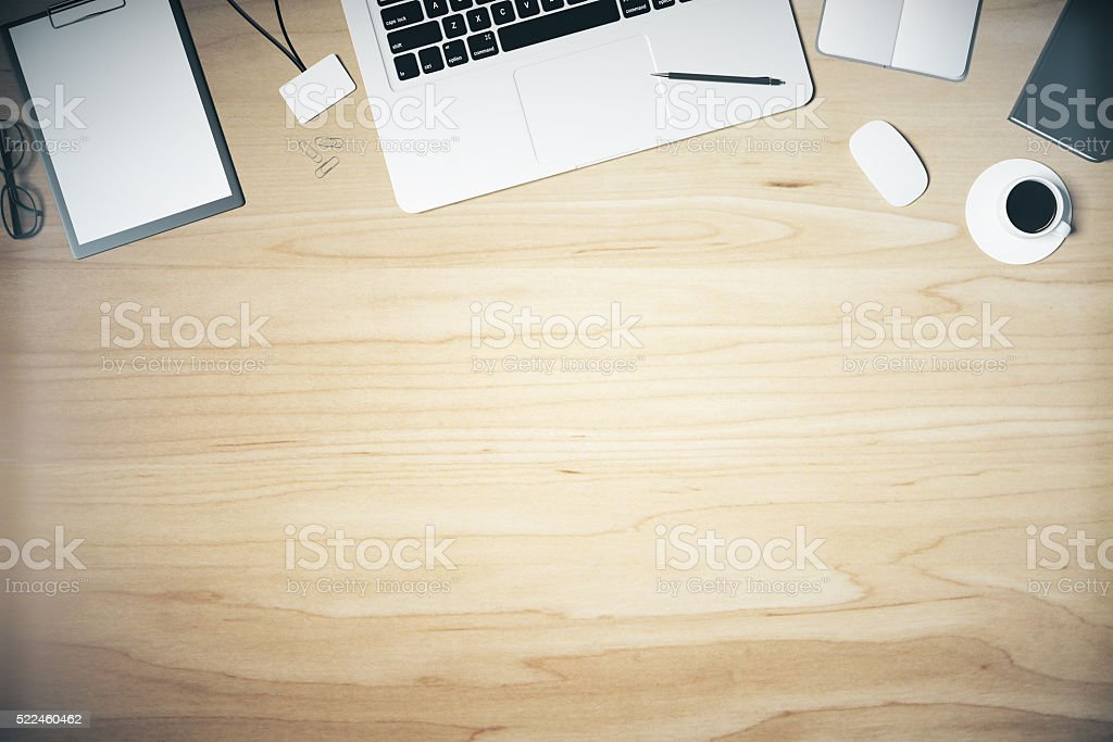 Wooden table with laptop, blank paper stock photo