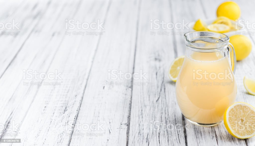 Wooden table with Lemon Juice (selective focus) stock photo
