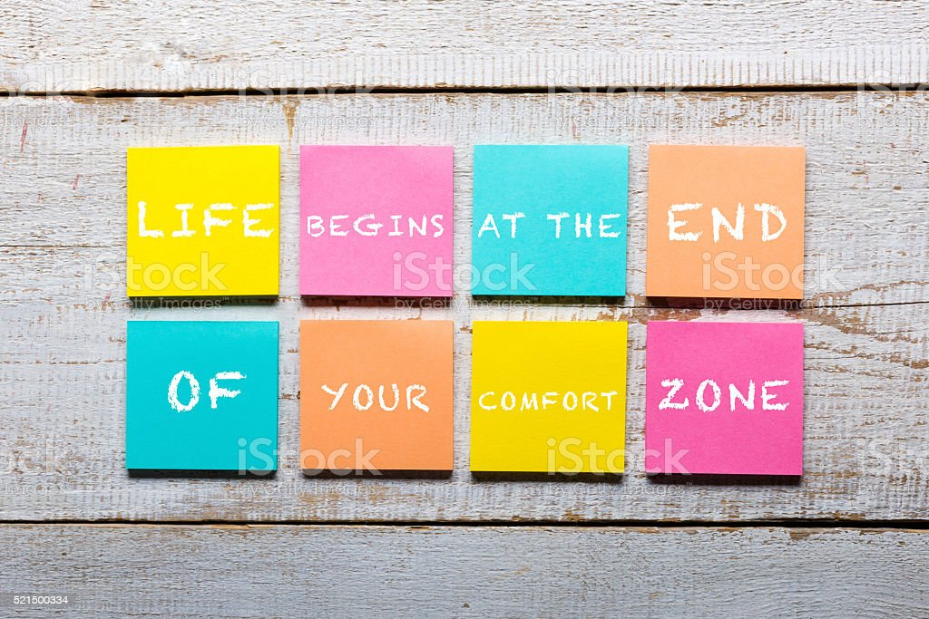 wooden table with motivational quote on colorful sticky notes stock photo