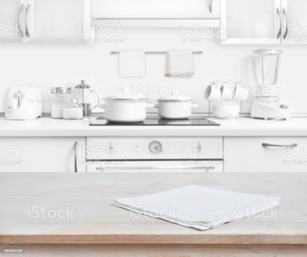 Wooden table with towel on blurred white modern kitchen background stock photo