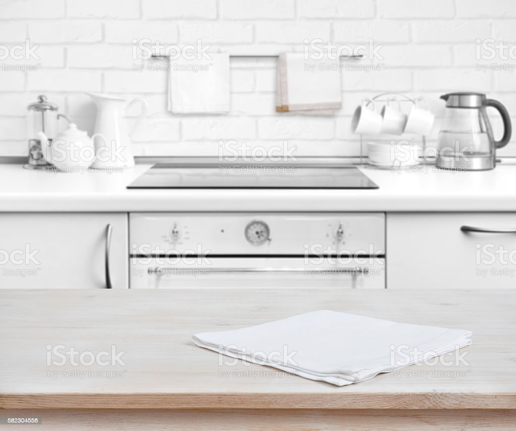 Wooden table with towel over defocused rustic kitchen bench background stock photo
