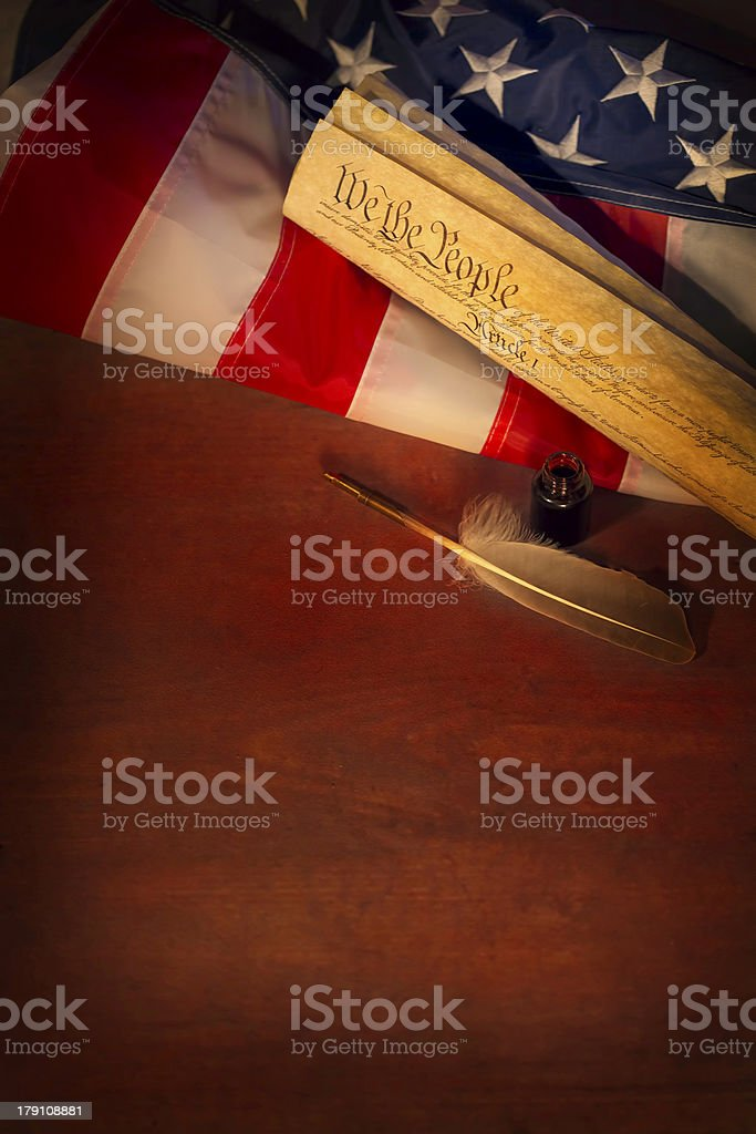 Wooden table with US Constitution, a quill and American flag stock photo