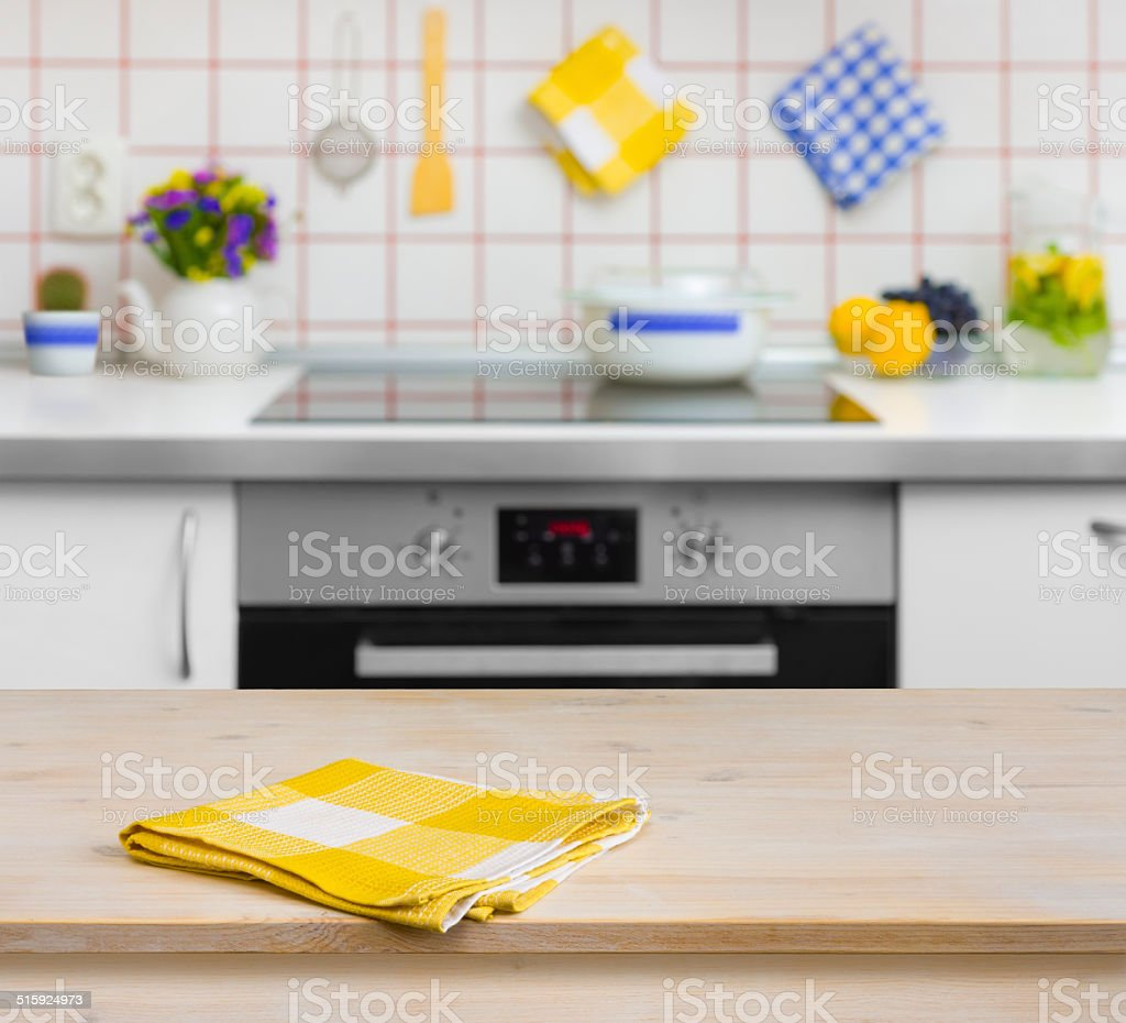 Wooden table with yellow napkin on kitchen background   Stock ...