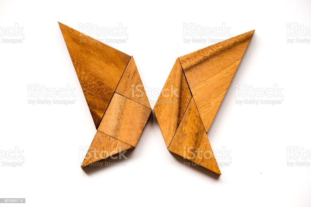Wooden tangram puzzle in butterfly shape on white background stock photo
