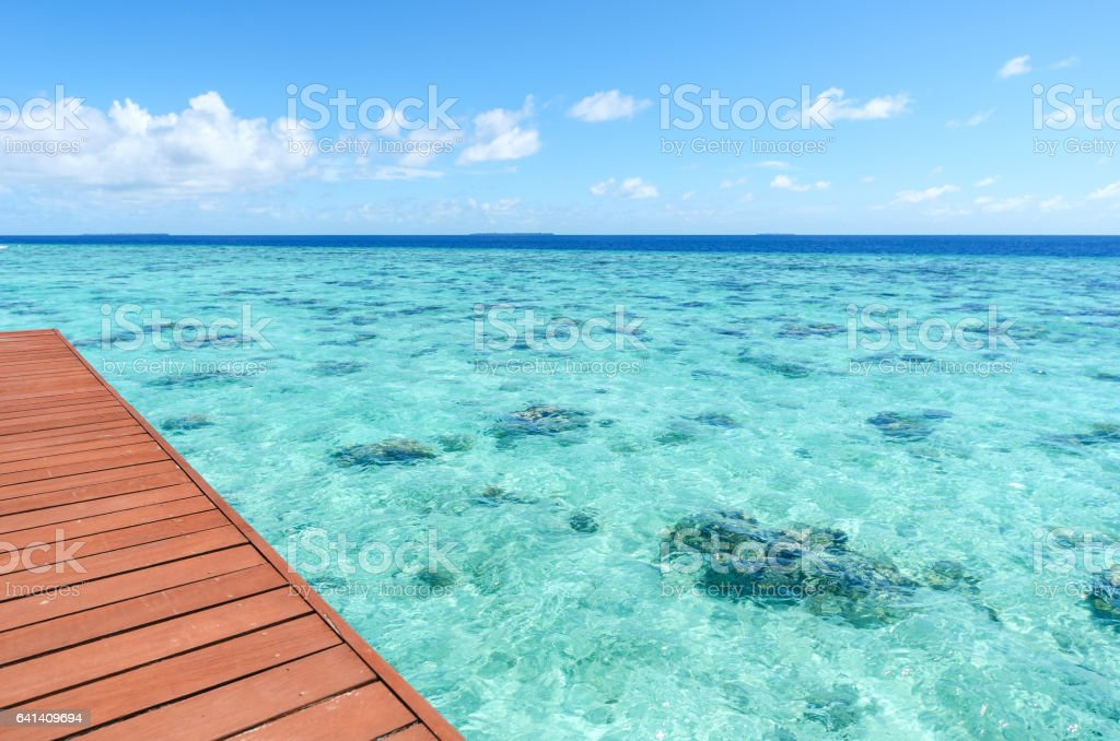Wooden terrace beside green tropical lagoon stock photo