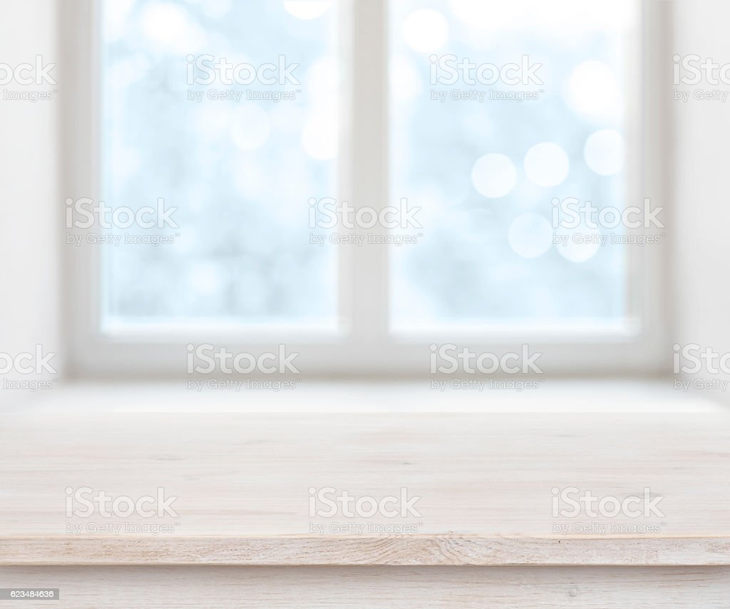Wooden texture table surface over abstract frosty winter window background stock photo