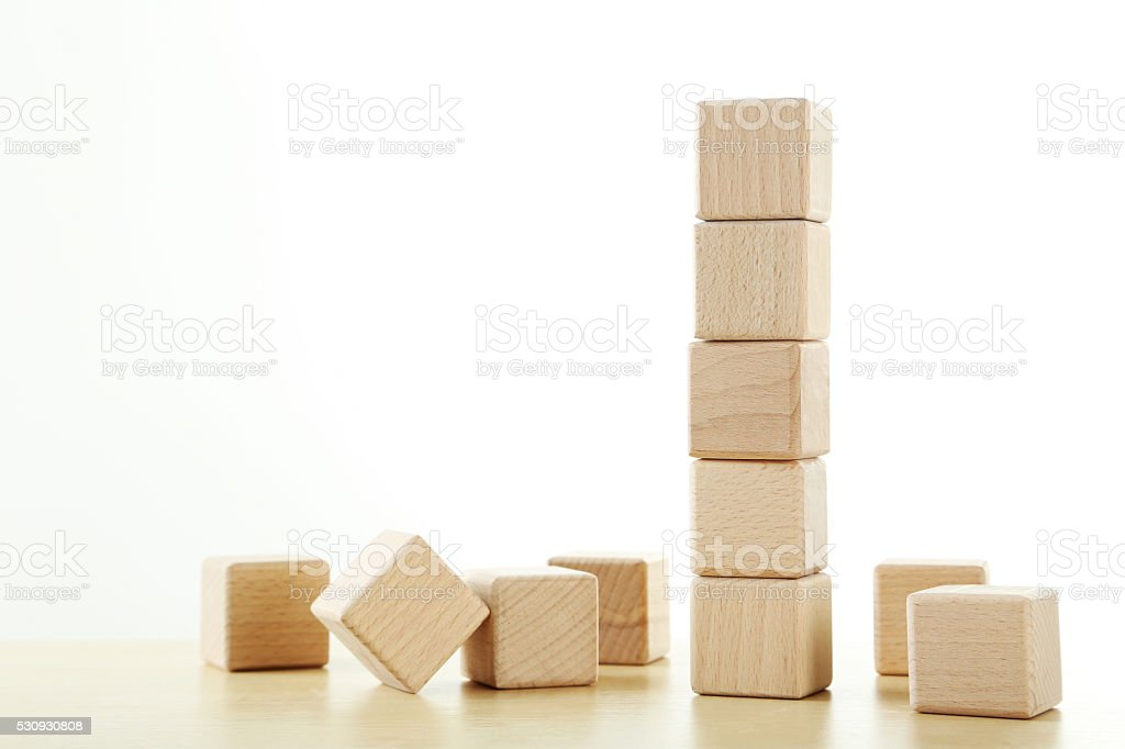 Wooden toy cubes on a brown wooden background stock photo