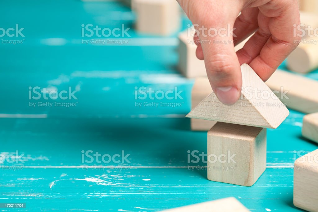 Wooden toy house with hand on white table stock photo