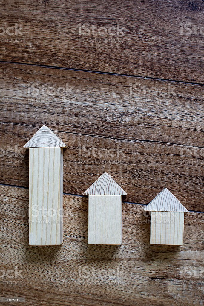 wooden toy houses in a row according to size stock photo