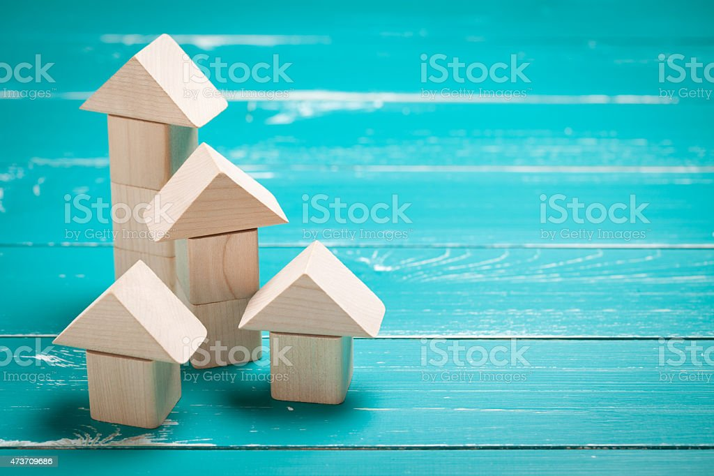 Wooden toy houses on turquoise table stock photo