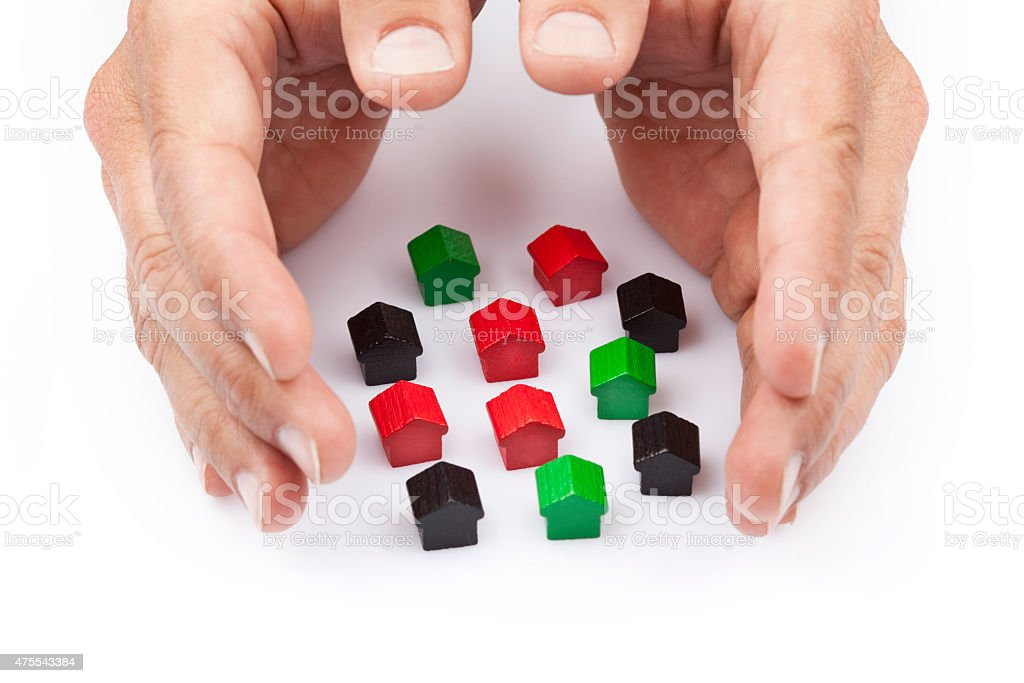 Wooden toy houses, protected by two hands stock photo