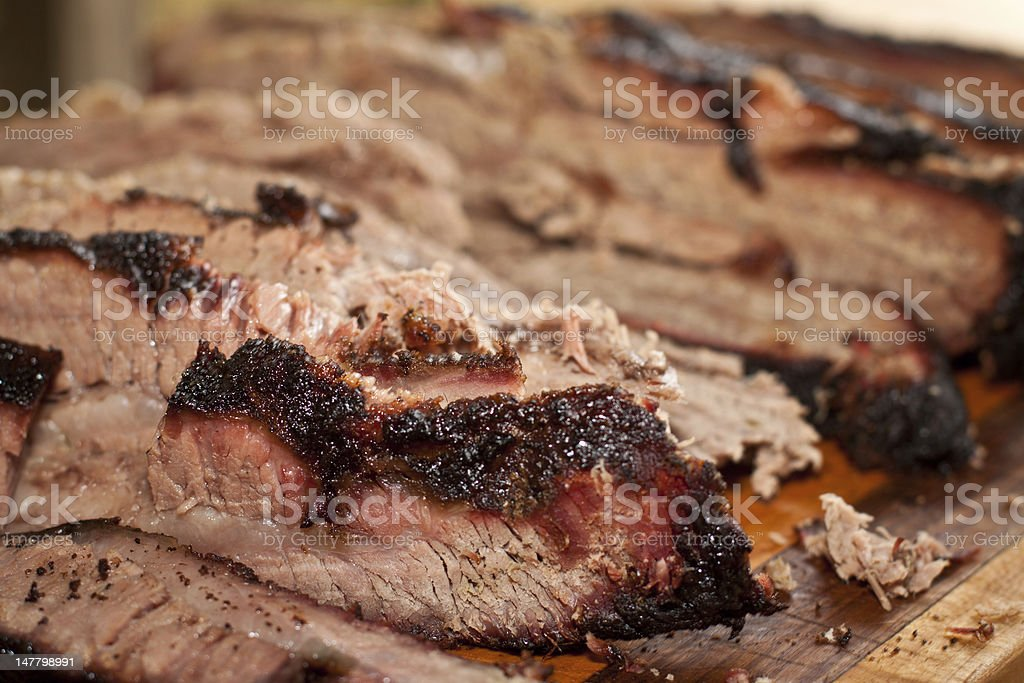 A wooden tray of sliced smoked brisket stock photo