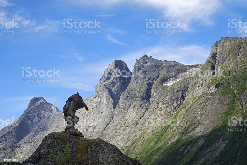 Wooden troll against mountain crest and blue sky. Trollstigen. stock photo