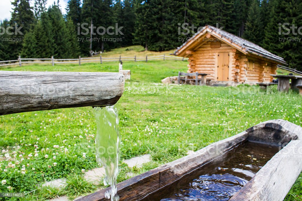 wooden trough with spring water in  a  farmhouse stock photo