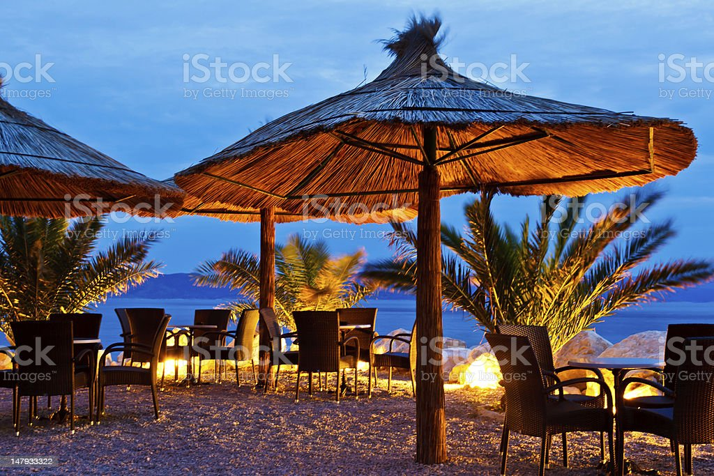 Wooden umbrellas on Pebble Beach at night, Brela, Croatia stock photo