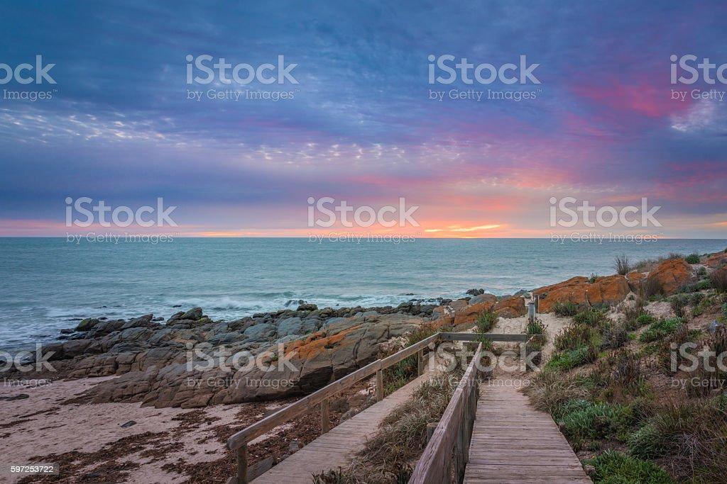 Wooden walk boards leading to rocky beach at dusk stock photo