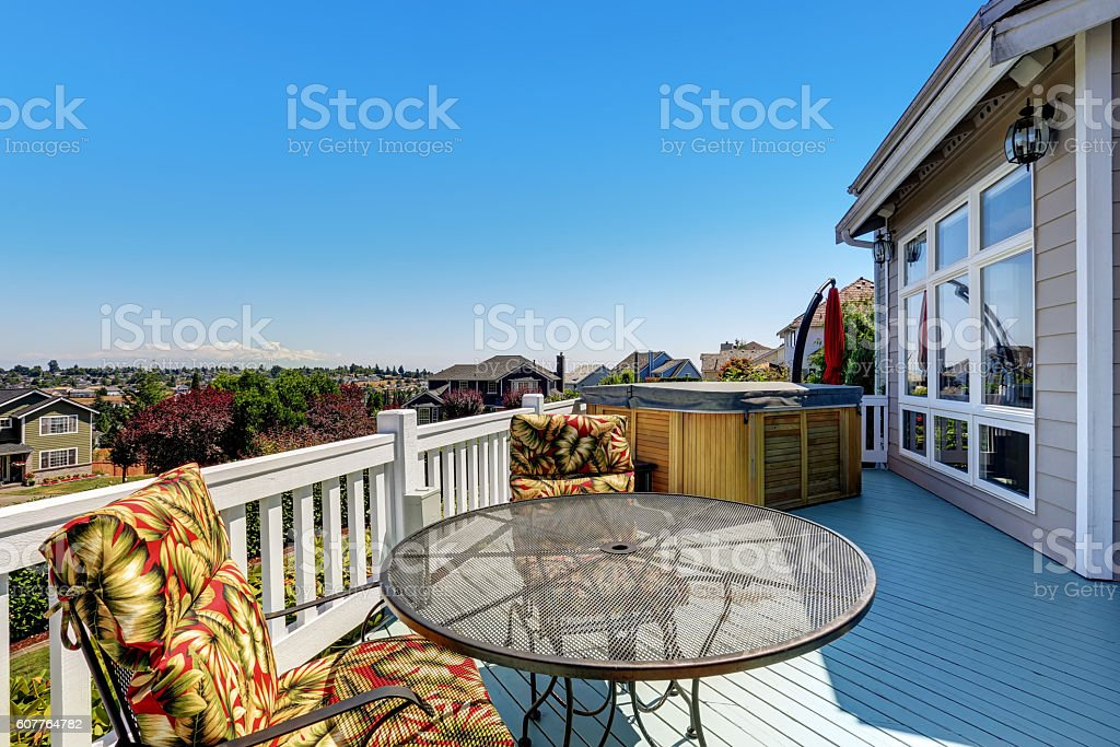Wooden walkout deck with outdoor settees and hot tub stock photo