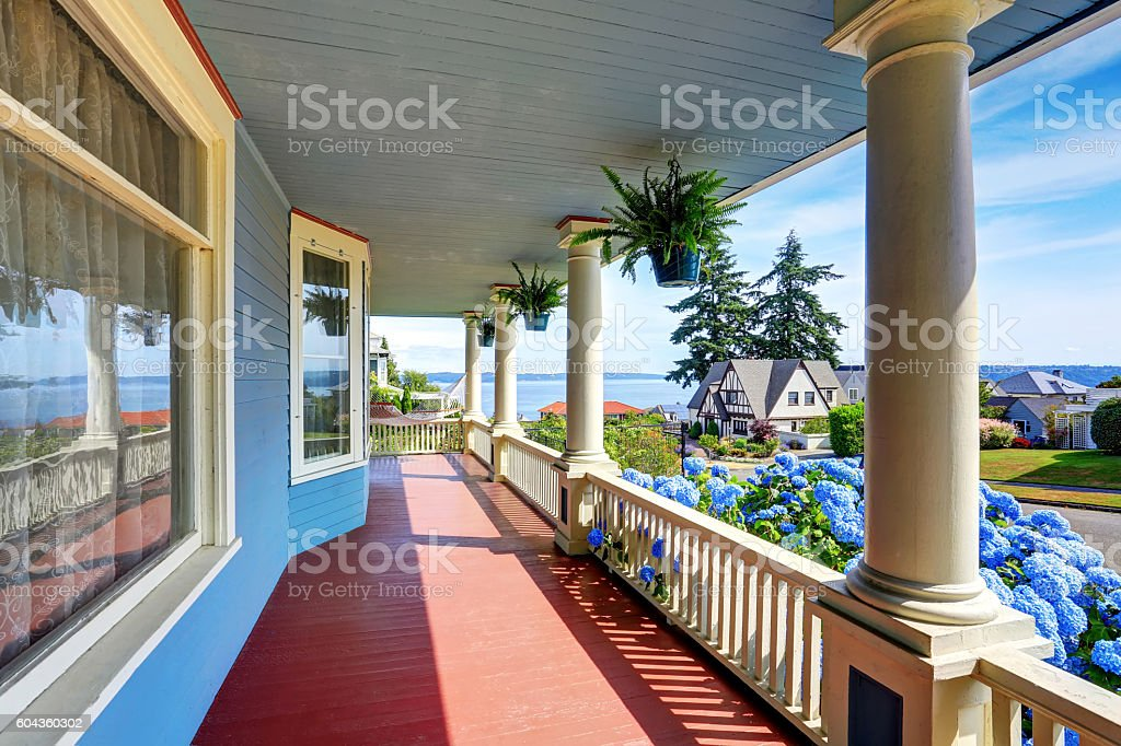Wooden walkout porch of craftsman American house in blue tones stock photo