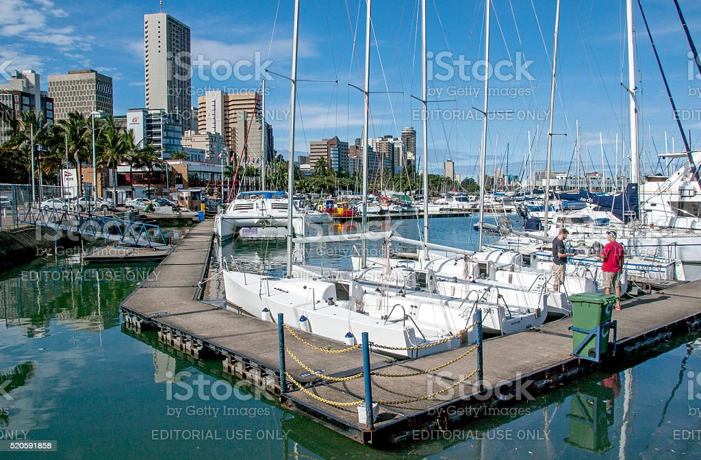 Wooden walkway and yachts against city skyline stock photo