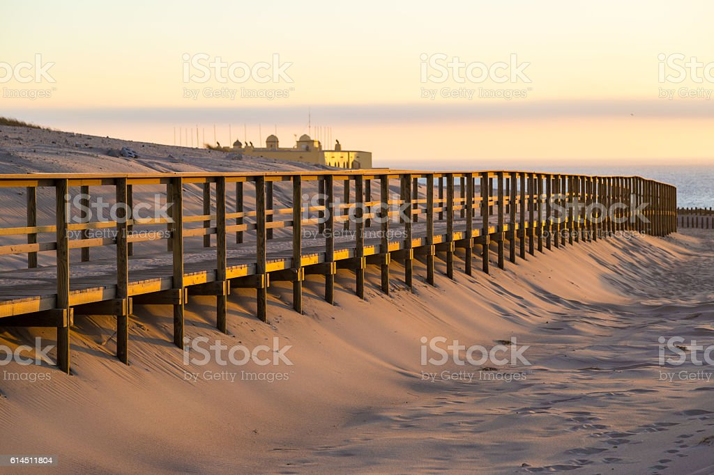 Wooden walkway in sand near Crismina beach at sunset, Portugal stock photo