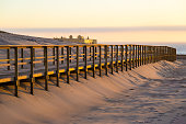 Wooden walkway in sand near Crismina beach at sunset, Portugal