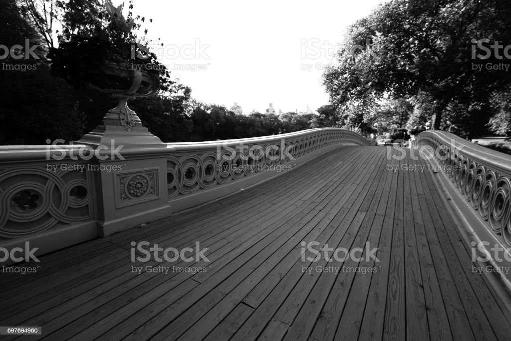 Wooden walkway of Bow bridge and trees at Central Park in black and white style stock photo