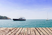 wooden walkway on sea and blue sky with boat