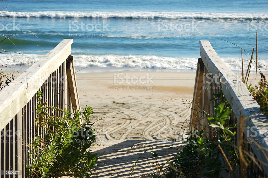 Wooden walkway to beach with ocean waves in background royalty-free stock photo