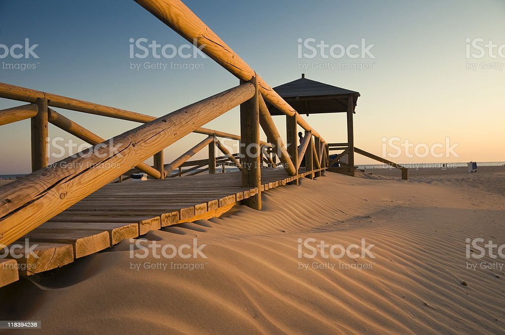 Wooden walkway view of sunset on Conil beach stock photo