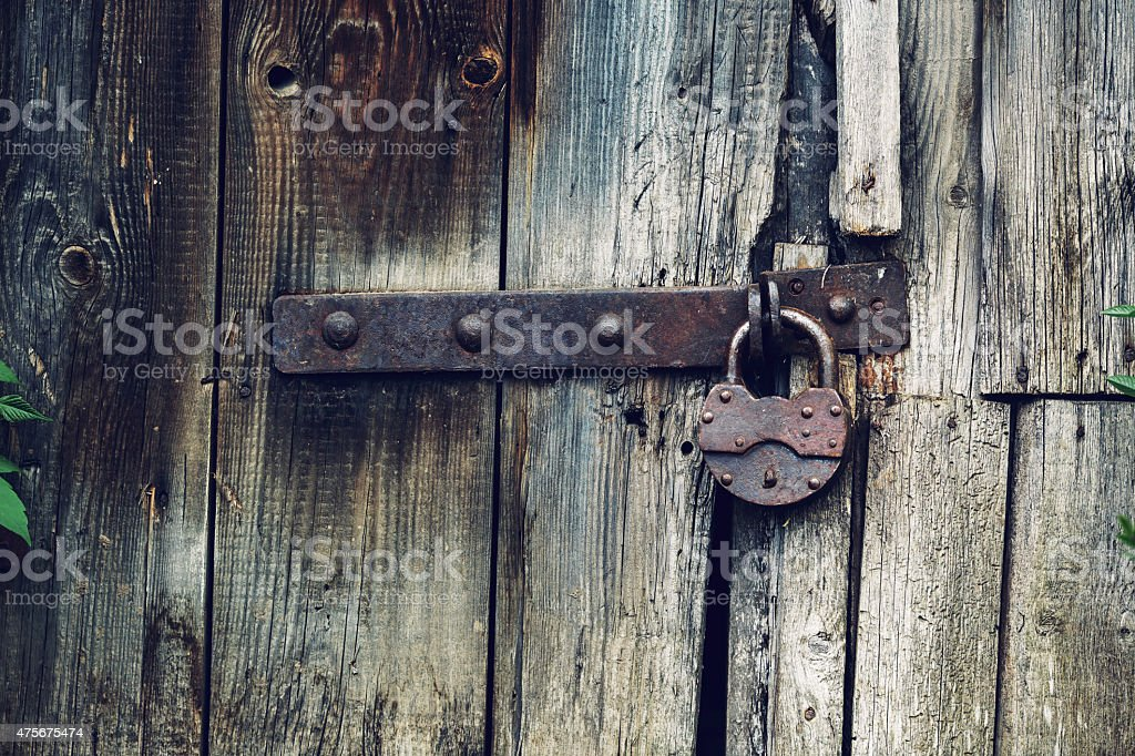 wooden wall and a door with an old rusty lock stock photo