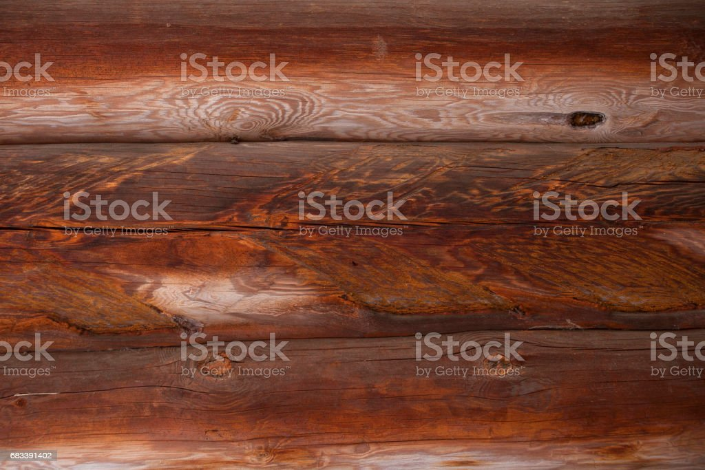 A wooden wall made of logs, faded and weathered, brownish-red, close-up stock photo