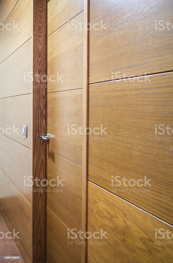 Wooden wall with door and a light switch royalty-free stock photo