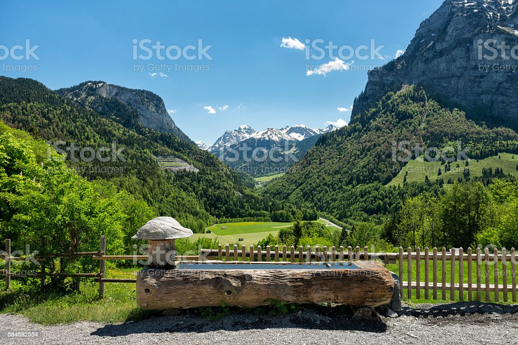 wooden well in the mountains stock photo