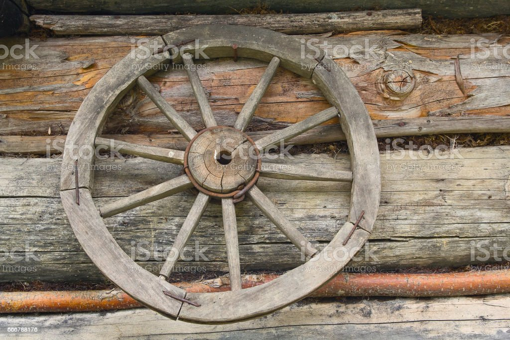 Wooden wheel from an ancient cart hanging on the wall stock photo