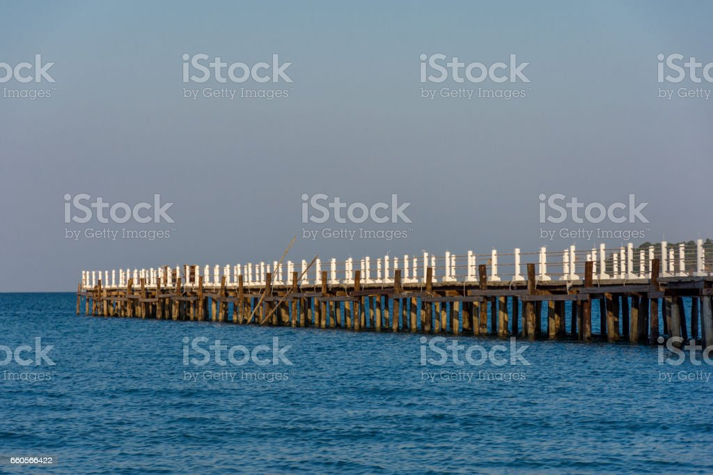 A wooden white posted jetty pier goes out in to a calm bay. stock photo