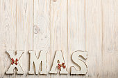 Wooden white XMAS letters on a white wooden background.