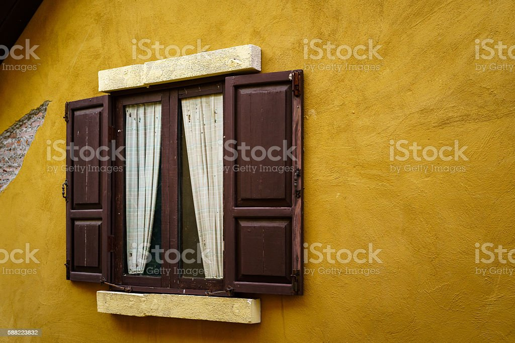 Wooden window with curtain on cracked yellow wall photo libre de droits
