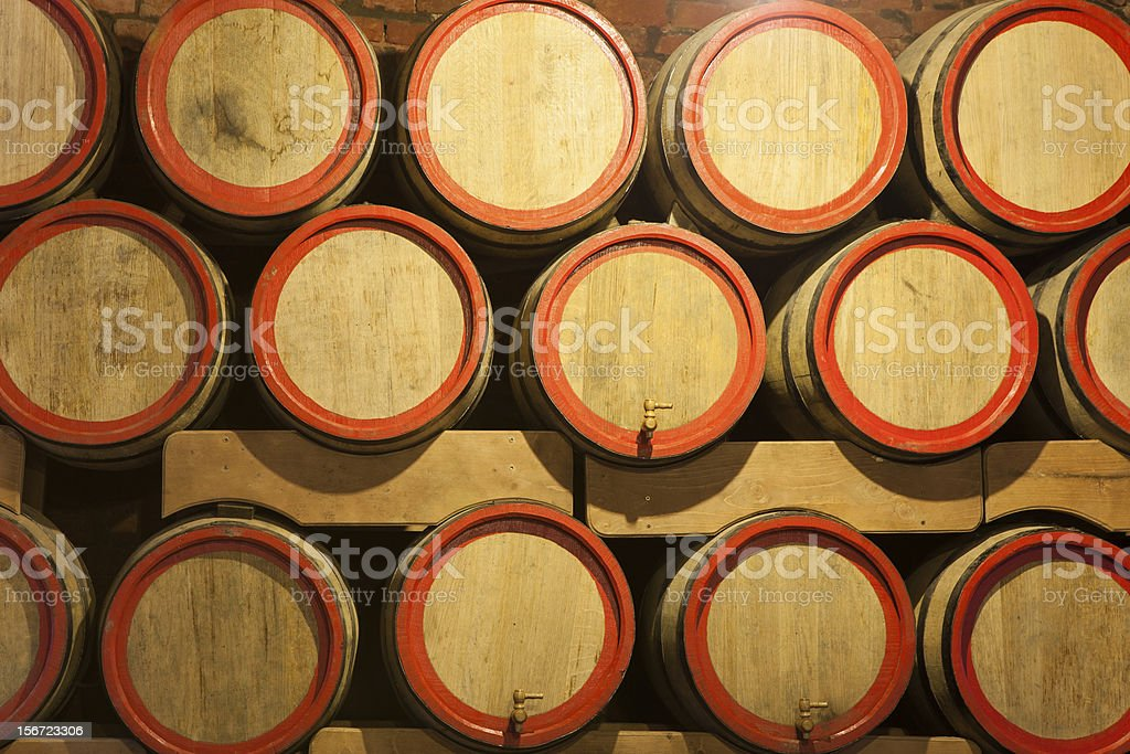 Wooden wine barrels are stored in winery cellar close-up royalty-free stock photo