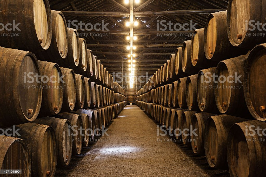 Wooden wine barrels stacked in neat lines in a port stock photo