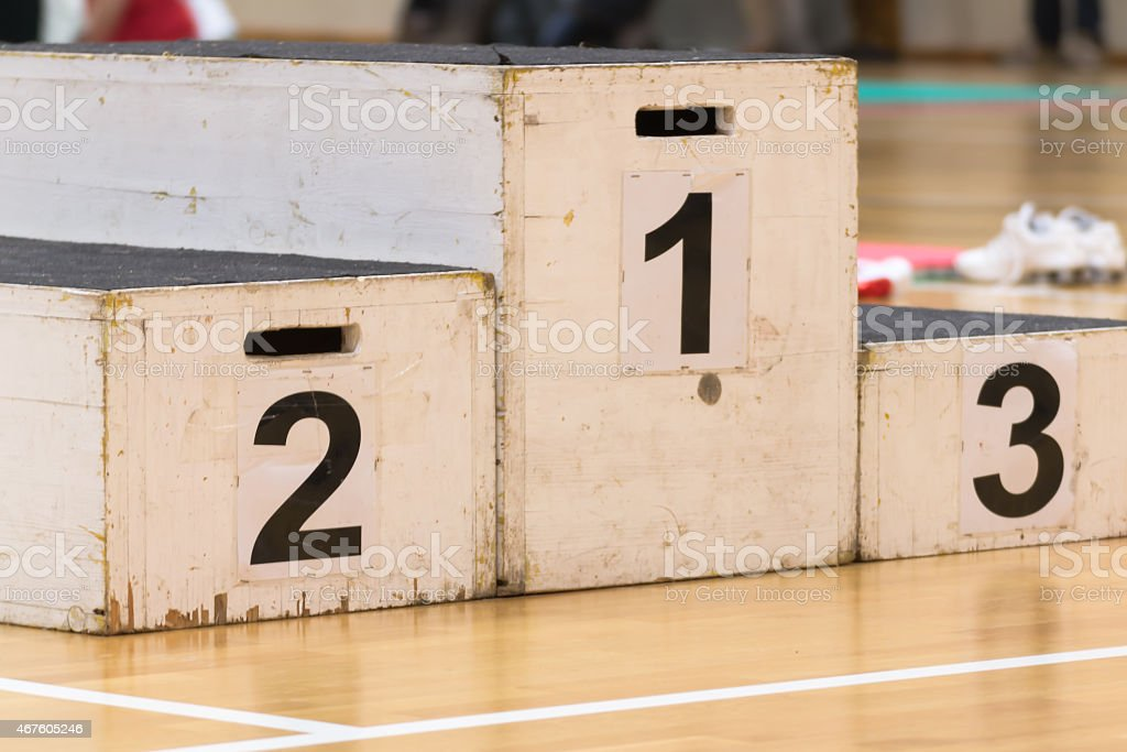A wooden winners' podium in a gym stock photo