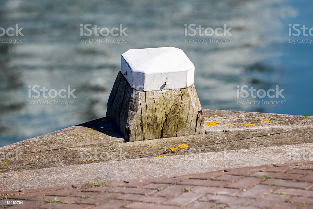 Wooden with white bollard in the harbour stock photo
