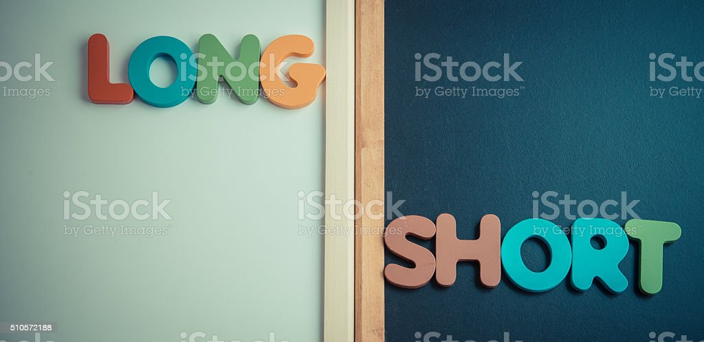 Wooden word LONG and SHORT on black and white board stock photo