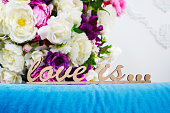 wooden words LOVE IS... against the background of a bouquet