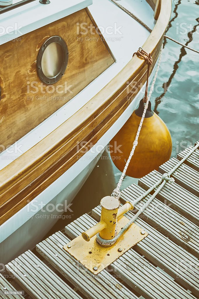 Wooden yacht moored to bollard in marina. stock photo