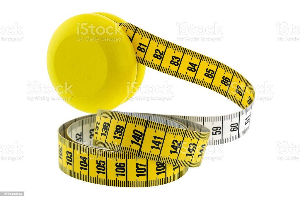 Wooden yellow YoYo with measuring tape represent Yo-Yo dieting Effect stock photo