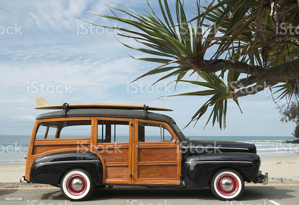 woodie car with surfboard on beach stock photo